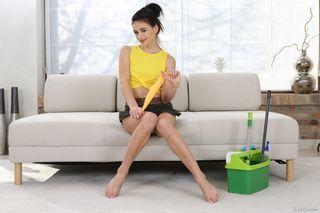 Брюнетка позирует в студии на диване и гладит рукой писечку