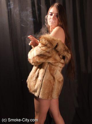 Красотка в шубе курит перед камерой и светит сиськами на фотографиях