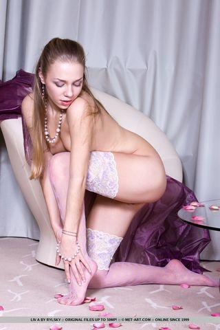 Девица в белых чулках и пеньюаре на фиолетовом кресле светит писечкой