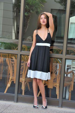 Модель задирает черно-белое платье и показывает на ступеньках на улице фотографу писюлю